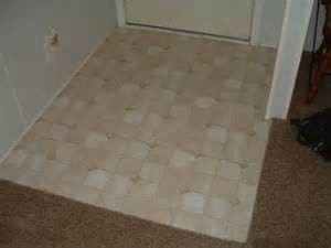 Laminate flooring at entry door surrounded by carpet