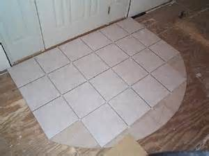 Ceramic tile at entry door surrounded by carpet